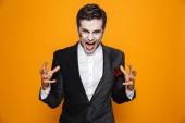 Fotografie Verärgerte Psycho Mann Zombie im Anzug schreien und suchen Kamera isoliert über orange