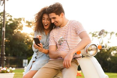 Portrait of young couple man and woman wearing earphones listening to music while sitting on motorbike together on city street