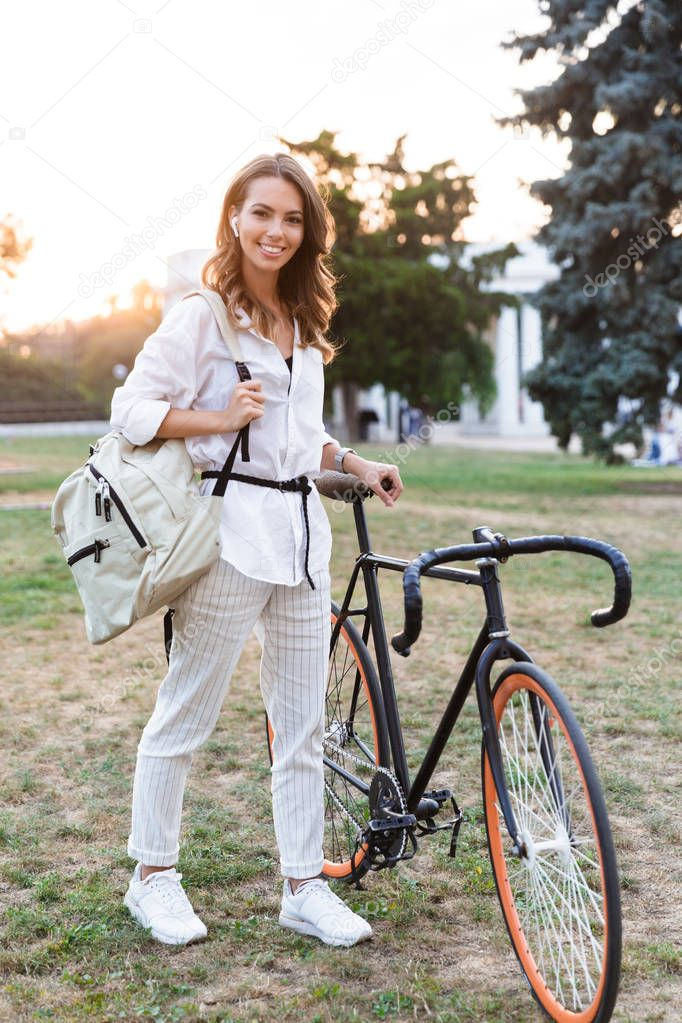 Image of cheerful cute young woman walking in park with bicycle listening music with earphones.