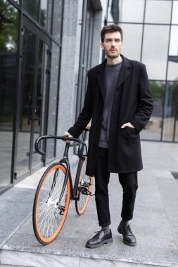 Image of handsome young business man walking outdoors with bicycle.