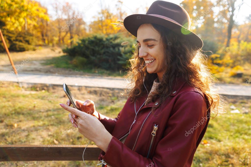 Image of a beautiful woman sitting walking in park using mobile phone listening music.