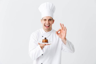 Cheerful man chef cook wearing uniform showing pastry on a plate isolated over white background