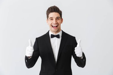 Portrait of a handsome young man waiter wearing tuxedo and gloves standing isolated over white background