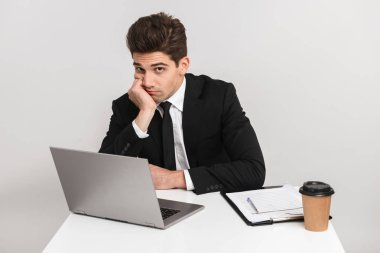 Tired bored young business man wearing suit isolated over gray background, sitting at the desk working on laptop