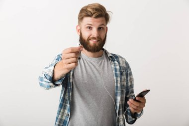 Image of a handsome young bearded man standing isolated over white wall background using mobile phone listening music.