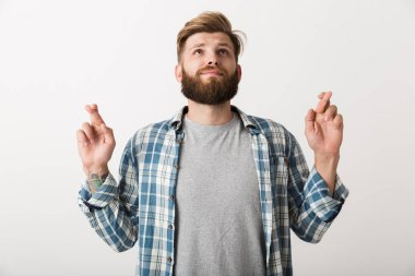 Worried bearded man dressed in plaid shirt standing isolated over white background, holding fingers crossed for good luck