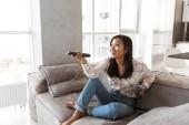 Fotografie z módní Asijské žena 20s hospodářství dálkové ovládání a sledování televize, zatímco sedí na pohovce v útulný byt