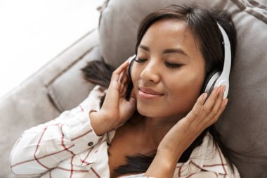 Photo of happy asian woman 20s wearing headphones listening to music while lying on sofa in living room