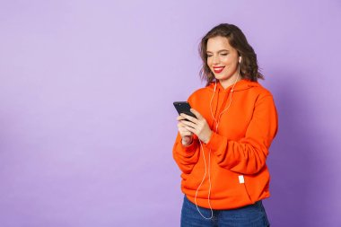 Image of an beautiful young woman posing isolated over purple background wall listening music with earphones.