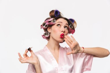 Pretty housewife with curlers in hair wearing robe standing isolated over white background, painting nails