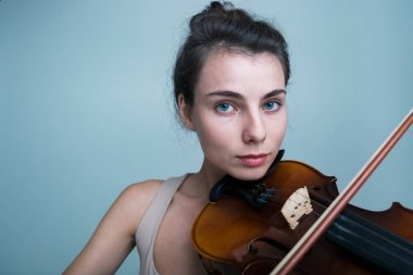 Close up portrait of a beautiful young woman posing with a violin isolated over blue background