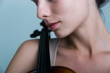 Cropped image of a beautiful young woman posing with a violin isolated over blue background
