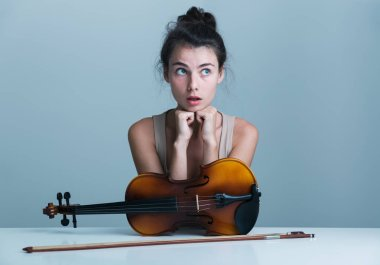 Portrait of a surprised beautiful young woman sitting at the table with a violin isolated over blue background