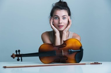 Portrait of a beautiful young woman sitting at the table with a violin isolated over blue background