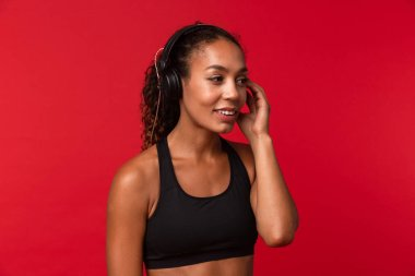 Portrait of joyful african american woman in black sportswear listening to music using headphones isolated over red background