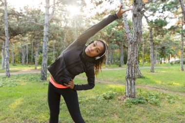 Image of energetic woman 20s wearing black tracksuit working out and stretching body in green park