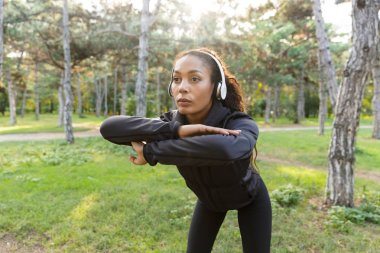 Image of beautiful woman 20s wearing black tracksuit working out and stretching body in green park