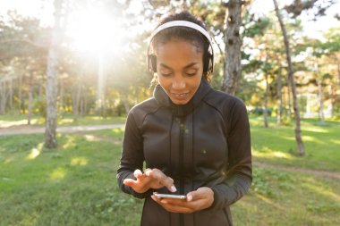 Image of beautiful woman 20s wearing black tracksuit and headphones using mobile phone while walking through green park
