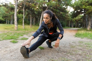 Portrait of fitness african american woman 20s wearing black tracksuit doing exercises and stretching her legs in green park