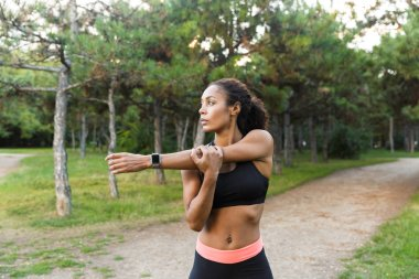 Young african american woman 20s wearing black tracksuit doing exercises and stretching her body in green park