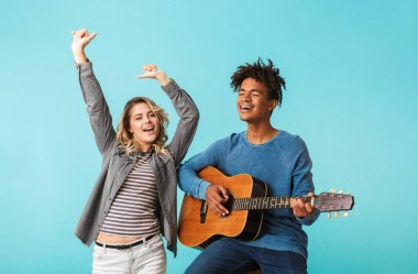 Happy young multiethninc couple together, playing a guitar isolated over blue background