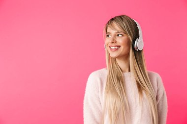 Cheerful young blonde girl standing isolated over pink background, listening to music with headphones