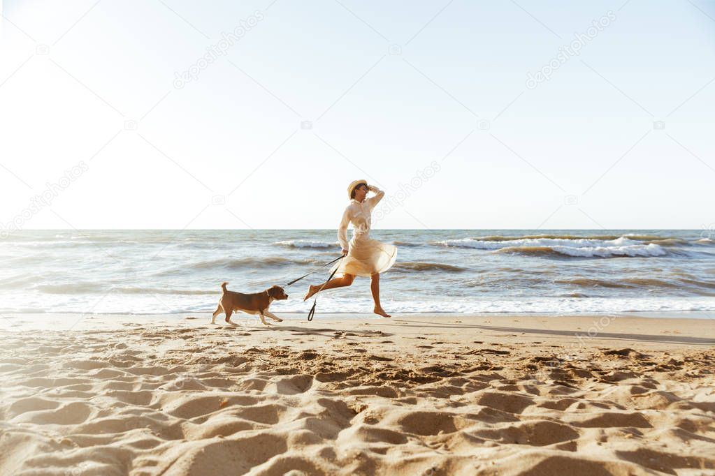 Image of beautiful woman in straw hat, running with her brown do