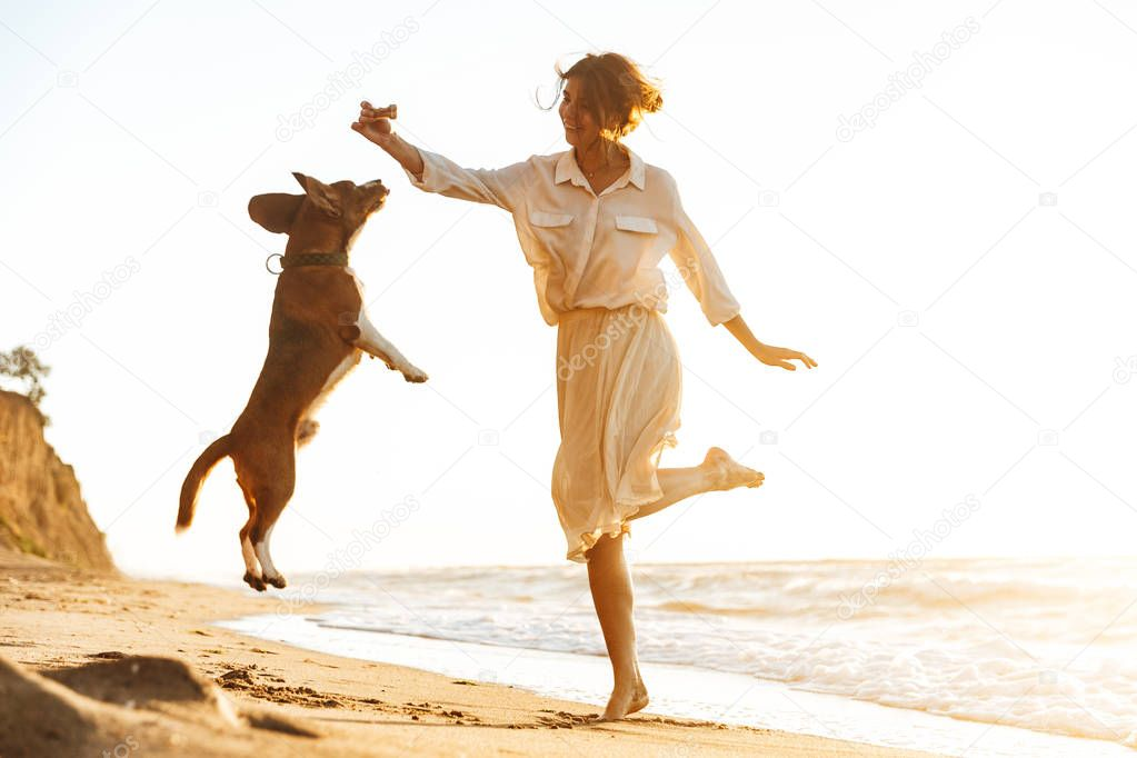 Image of happy woman 20s playing with her dog, while walking by