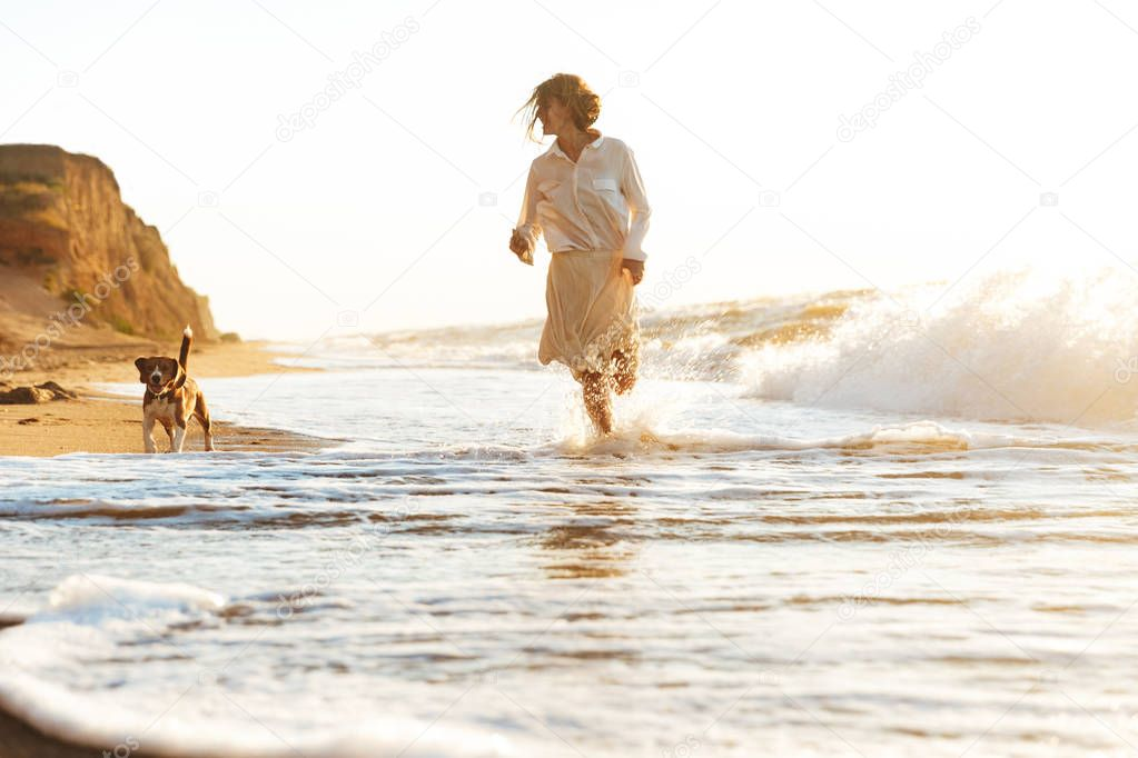 Image of lovely woman 20s running with her dog, by seaside in th