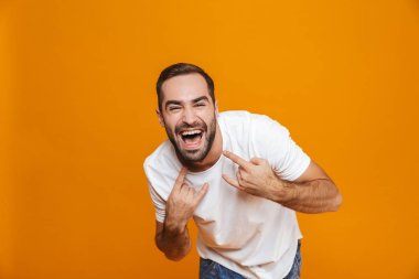 Image of happy guy 30s in t-shirt rejoicing and showing rock sig