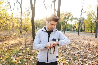 Young sportsman outdoors in park listening music with earphones drinking water looking at watch.