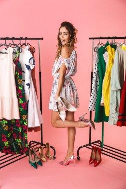 Full length photo of joyful woman near wardrobe with clothes cho