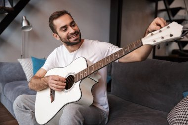 Photo of caucasian man playing acoustic guitar while sitting on