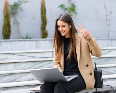 Beautiful young woman wearing autumn coat using laptop
