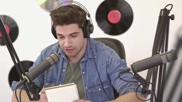 Photo Cheerful handsome DJ man in denim jacket using smartphone broadcast on radio
