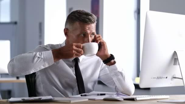 ernsthafter, konzentrierter Geschäftsmann im weißen Hemd telefoniert und trinkt während der Arbeit im Büro Kaffee