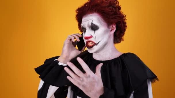 Boldog misztikus bohóc a Halloween smink beszél smartphone felett narancssárga háttér