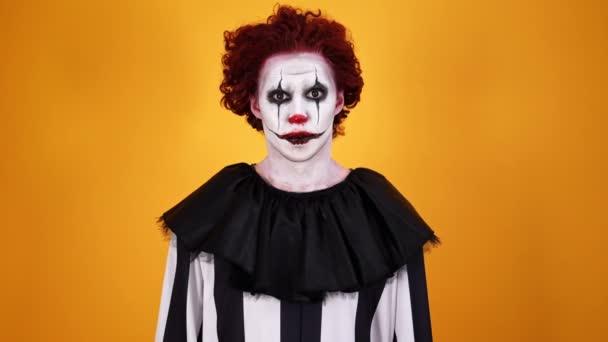Játékos meglepett bohóc Halloween smink nézi a kamerát narancssárga háttér