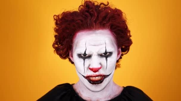 Közelről kilátás dühös bohóc a Halloween-smink, és a kamera nézi a kamerát narancssárga háttér