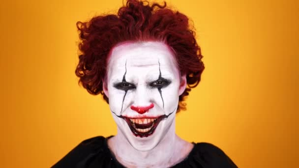 Közeli kilátás dühös nevetve bohóc Halloween smink nézi a kamerát narancssárga háttér