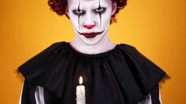 Közelről kilátás dühös bohóc a Halloween smink gazdaság gyertyát, és nézte a kamerát narancssárga háttér