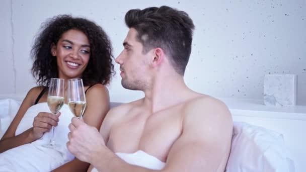 Lächeln liebendes multiethnisches Paar trinkt Champagner und redet im Bett