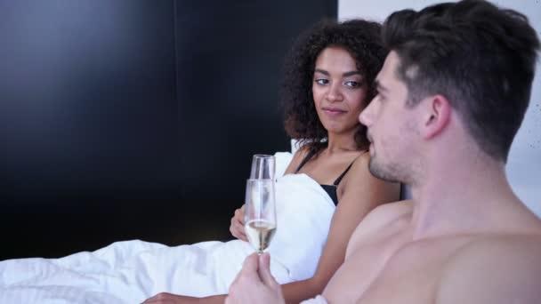 Seitenansicht eines lächelnden liebenden multiethnischen Paares, das Champagner trinkt und im Bett spricht