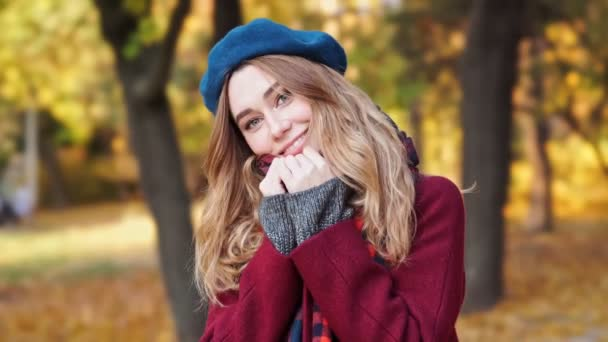 Close up view of Smiling brunette woman in beret hat and coat looking at camera while walks in park