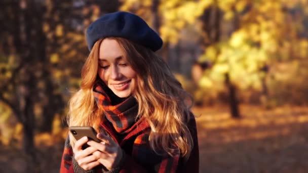 glückliche brünette Frau mit Baskenmütze und Mantel mit Smartphone im Park