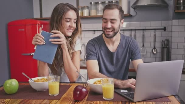 Happy lovely couple having breakfast and using laptop computer while sitting together on kitchen