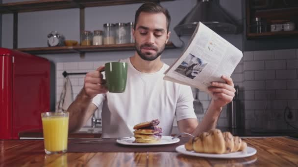 Smiling handsome bearded man having breakfast and reading newspaper while sitting by the table at home