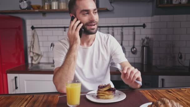 Happy handsome bearded man having breakfast and talking by smartphone while sitting by the table at home