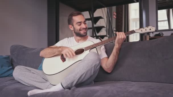 Happy handsome bearded man playing on guitar while sitting on sofa at home