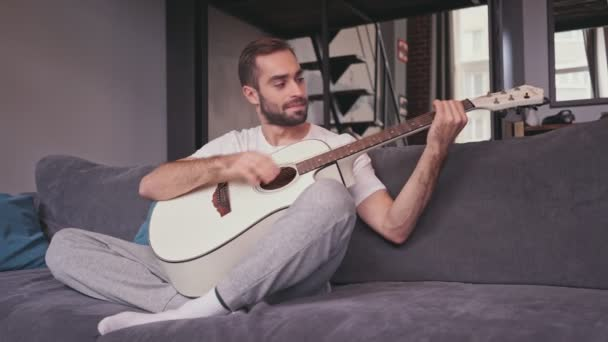 Smiling handsome bearded man playing on guitar while sitting on sofa at home
